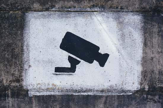 A painting on a wall warning visitors about video surveillance. @tobiastu, unsplash.com.